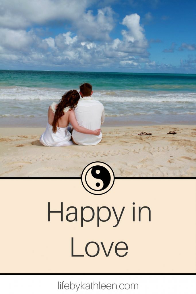 couple on a beach text overlay happy in love